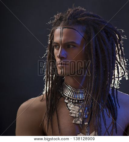 Young man's portrait. Stylish handsome sexy Guy with Dreadlocks and ethnic Jewelry Accessories (necklace bracelet) Close-up face. Tribal Style. Trendy youthful man's look war paint