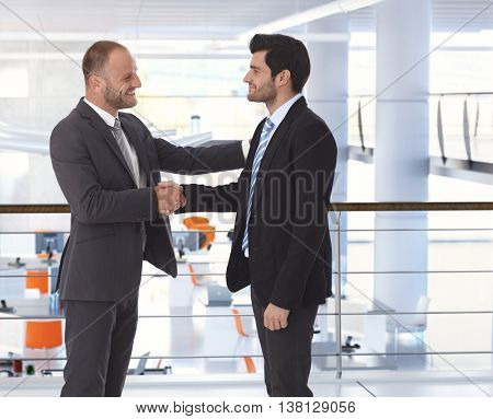 Happy handsome caucasian bristly businessman shaking hands on business deal at office. Hand on shoulder, side view, copyspace, suit.