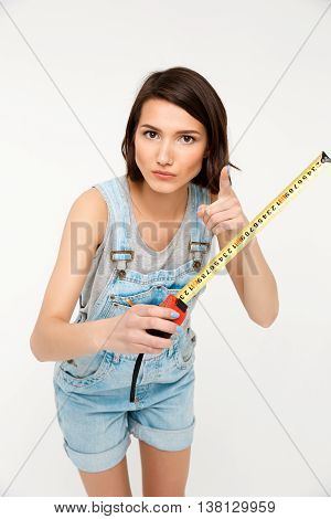 A portrait of young serious beautiful girl, in gray shirt and denim overall, holding tape measure, pointing forward with finger, looking at camera, isolated on white background