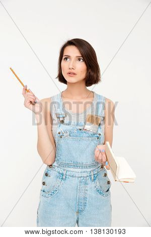 A portrait of thinking young beautiful girl, in gray shirt and denim overall, holding notebook, isolated on white background