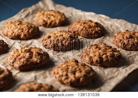 Cropped image of oatmeal cookies with nuts on a baking tray with parchment paper, selective focus