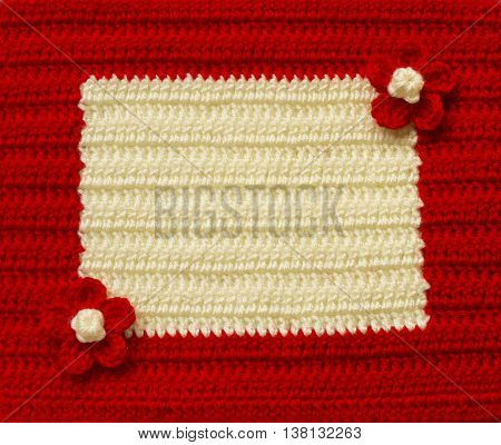Handmade red and white crochet frame pattern knitting sewing. Homemade colorful backdrop with flowers. Background for sketchbook notebook Christmas yuletide Valentine's day. Place for text.