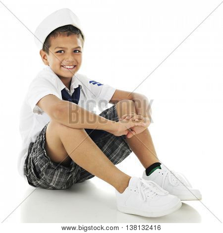 A wanna-be sailor happily sitting in his sailor hat, shirt and tie as he waits a boa ride.  On a white background.