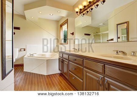 Master Bathroom Interior With Brown Cabinets, Large Mirror With Lights And White Bathtub.