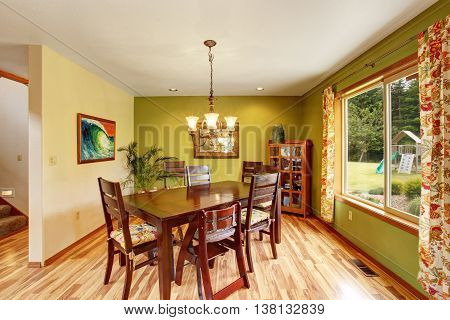 Antique Green Dining Room Interior With Mahogany Table Set And Chandelier.