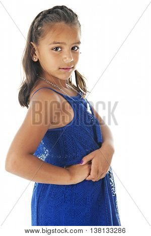 A beautiful elementary Hispanic girl looking back at the viewer in her lacy royal blue summer dress.  On a white background.