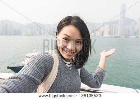 Young Asian woman take a selfie at Victoria Harbor, Hong Kong.