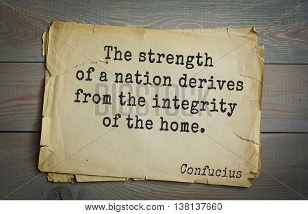Ancient chinese philosopher Confucius quote on old paper background. The strength of a nation derives from the integrity of the home.