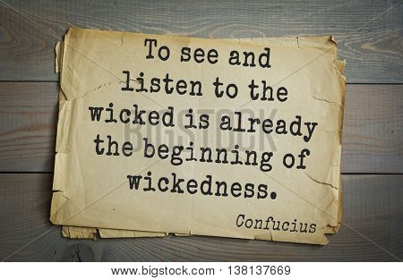 Ancient chinese philosopher Confucius quote on old paper background. To see and listen to the wicked is already the beginning of wickedness.