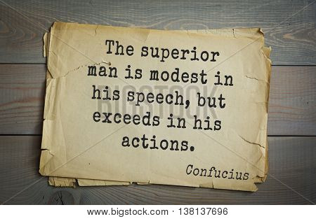 Ancient chinese philosopher Confucius quote on old paper background. The superior man is modest in his speech, but exceeds in his actions.