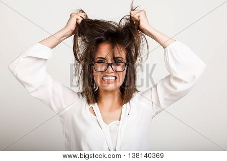 Close up portrait of upset business lady with tousled hair in glasses.