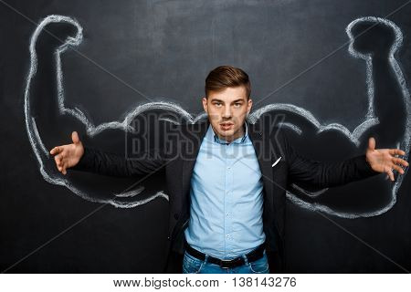 Picture of  mad, angry suited business  man with  fake muscle arms over blackboard.