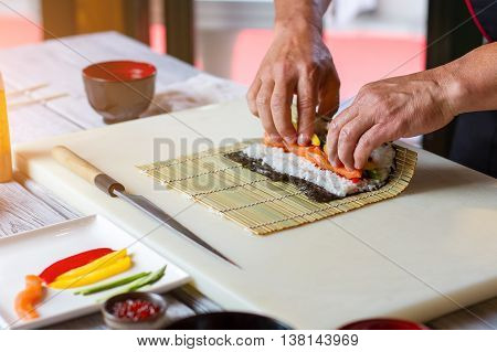 Man's hands touch bamboo mat. Nori leaf and raw fish. Sushi chef prepares futomaki rolls. Only fresh and quality ingredients.