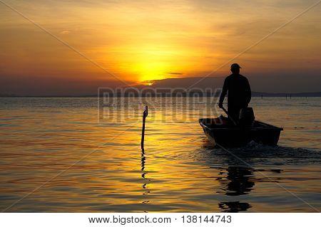 Silhouette of fisherman on boat in the sunrise at Labuan island,Malaysia.
