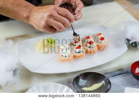 Spoon puts caviar onto sushi. Plate with sushi rolls. Steam coming from dry ice. Uramaki rolls with salted caviar.