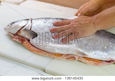 Man's hand touches raw fish. Knife cuts big fish. Fresh salmon on cooking board. Quality product from the supermarket.
