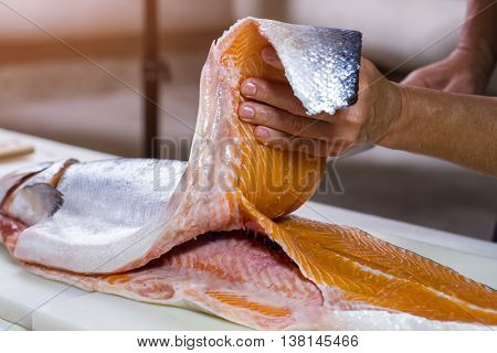 Man's hand holds fish meat. Meat of raw fish. Best salmon for cooking sushi. Lots of calories and protein. poster
