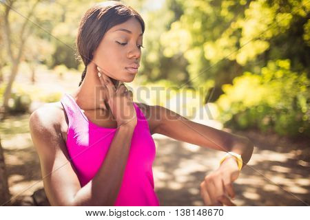 Woman touching her pulsation at park