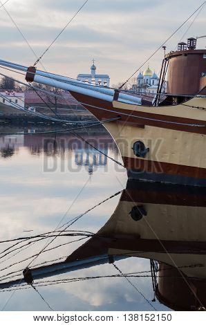 Architecture spring travel landscape - Novgorod Kremlin fortress and St Sophia cathedral on the bank of the Volkhov river with bow of the frigate ship with rigging on the foreground