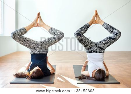 Two Young Women Doing Yoga Asana Bound Angle Shoulderstand Pose