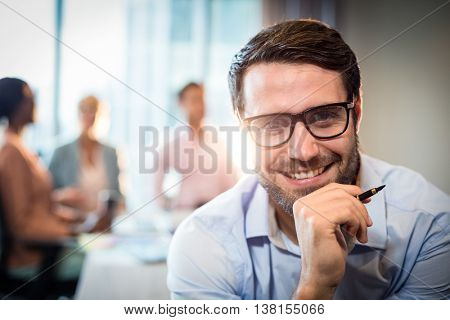 Portrait of a man with hand on chin while coworker interacting in the background in the office