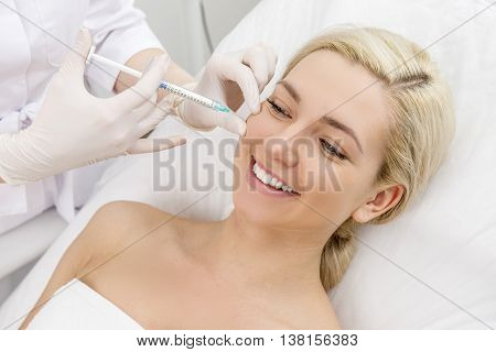 Beautiful woman gets beauty facial injections. Face aging injection. Aesthetic Cosmetology