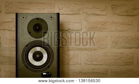 Vintage speaker system against a background of a brick wall