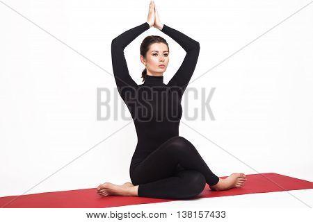 Beautiful athletic girl in a black suit doing yoga. gomukhasana asana - pose cow's head. Isolated on white background.