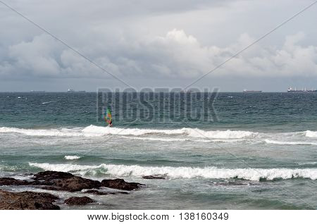 DURBAN SOUTH AFRICA - JULY 09 2016: Windsurfers in the waves at Umhlanga Rocks with shipping on the Indian Ocean in the background.