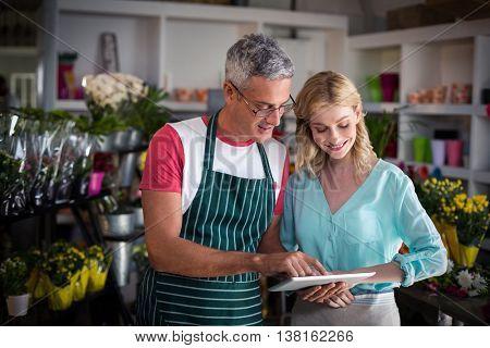 Smiling florists using digital tablet in florist shop