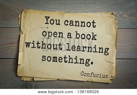 Ancient chinese philosopher Confucius quote on old paper background. You cannot open a book without learning something.
