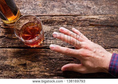 man reaches to alcohol on wooden background