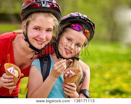 Bikes bicyclist girl. Girls wearing bicycle helmet with rucksack rides bicycle in summer park. Happy girls biking eating ice cream cone . Bicyclist is looking at camera.