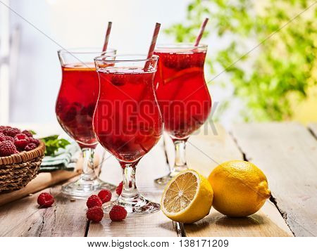 Wooden boards are ice cold beverage glasses with red raspberry lemon cocktail . Alcohol country cocktail beverage number hundred thirty six with raspberry basket. Cocktail beverage corporate outdoor.