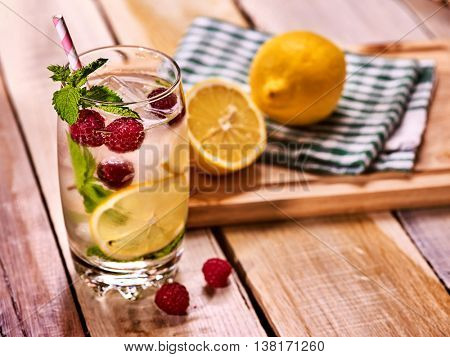 Alcohol cocktail. On wooden boards glass with raspberry alcohol cocktail and ice cubes. Drink number hundred nineteen cocktail raspberry mojito with lime and mint leaf. Country life. Light background.