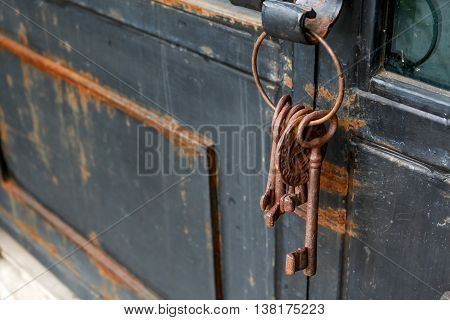 some old and rusty keys chain on a rustic door