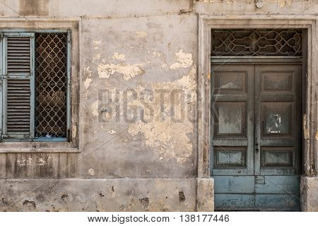 Traditional Maltese ancient wooden doorway and window with faded paint shot straight-on in Valletta Malta Europe. Used in the 2015 filming of the Assassin's Creed movie.