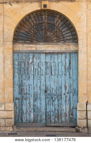 Traditional Maltese ancient blue wooden doorway with flaking paint shot straight-on in Valletta Malta Europe. Used in the 2015 filming of the Assassin's Creed movie.