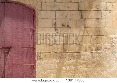 Locked red wooden double-door in Maltese Limestone wall shot straight-on in Valletta Malta Europe. Used in the 2015 filming of the Assassin's Creed movie.
