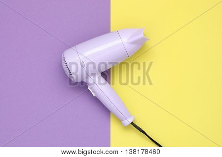Purple hair dryer on purple and yellow paper background