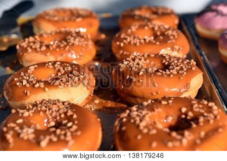 Fresh donuts with caramel in a storefront
