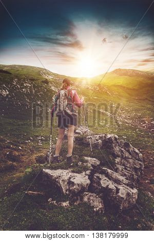 Young woman hiking in the alps at sunrise standing with her back to the camera on a rocky outcrop on a steep mountain slop