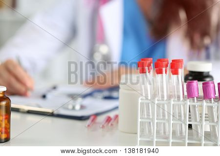 Close up view of medical flasks with doctor intern or student working at background in laboratory. Scientific research healthcare and medical concept.