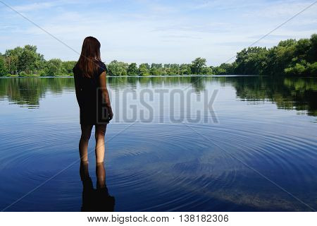 rear view of young woman standing in lake in solitude