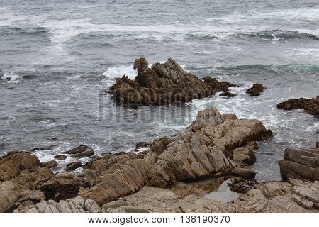An up close view of the rocky coastline of Pacific Grove, California with gentle waves of  greyish blue water with shades of aqua and white foam splashing over the jagged rocks