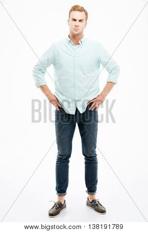 Full length of angry strict young man standing with hands on hips over white background