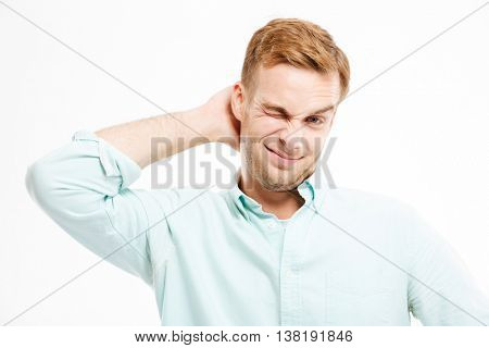 Lazy handsome young businessman standing and scratching his head over white background