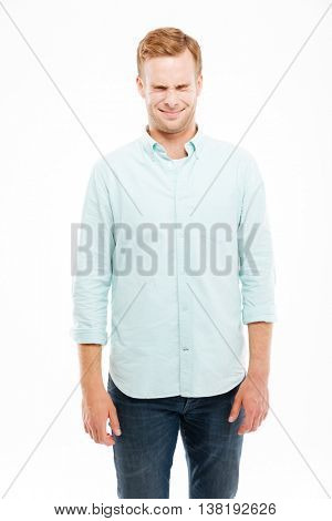 Smiling cute young man standing and squinting over white background