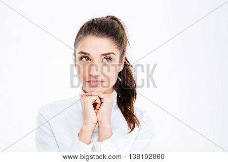 Thinking business woman smiling and looking up at copy space over white background