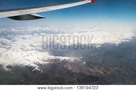View of jet plane wing. Above mountain